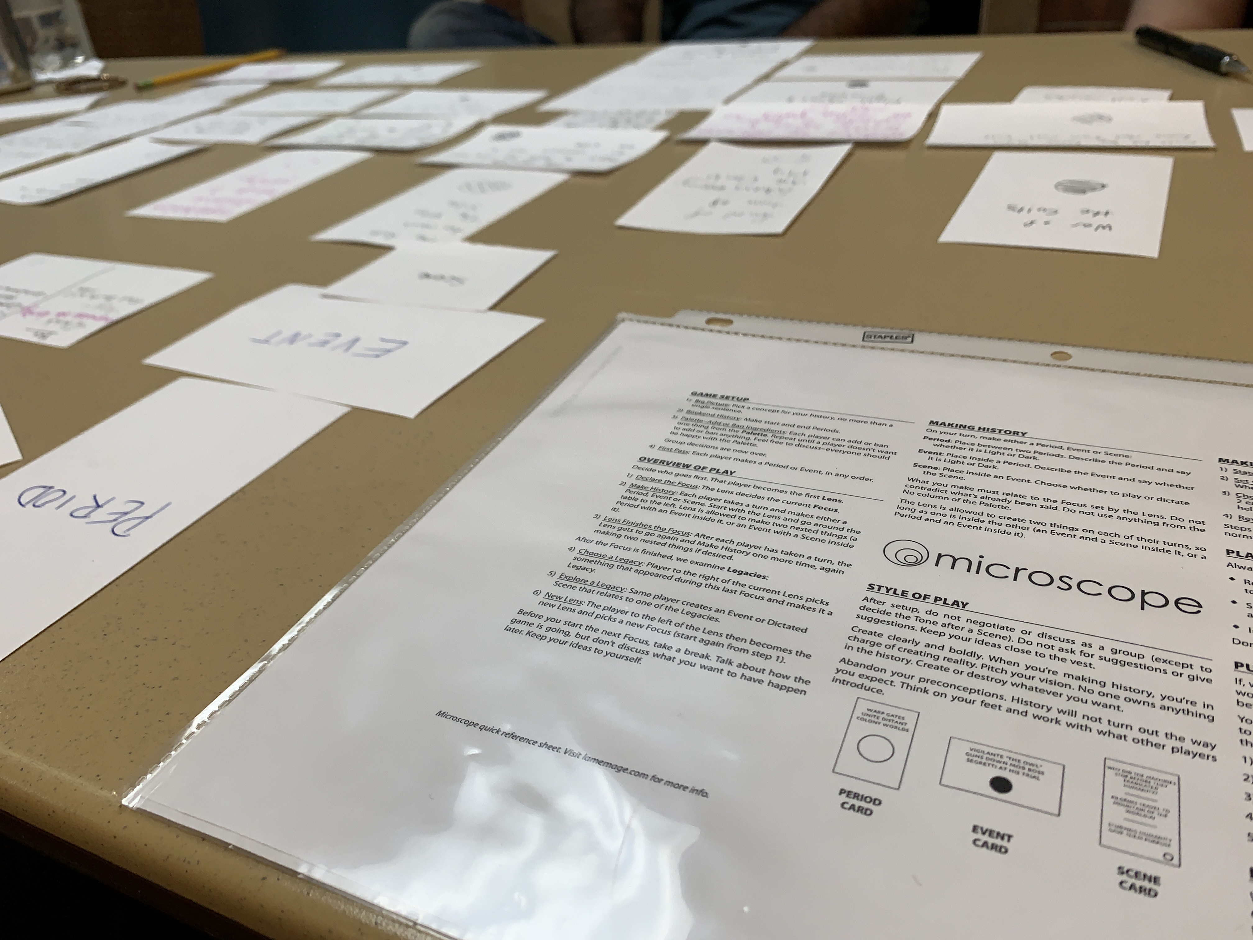 Gaming table showing index cards laid out in a tableau and the Microscope quick guide.