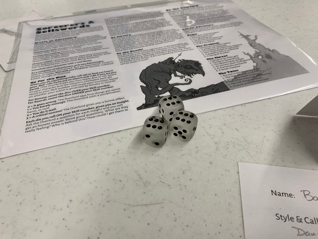 Copy of Sorcerors & Sellswords sits upon a table with 3 dice showing 6s up atop it.